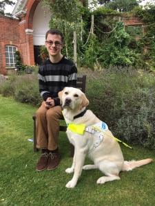 Photo shows a photo of me and Guide Dog Blossom sitting in a house garden posing for a photo. Blossom is wear her Guide Dog harness.