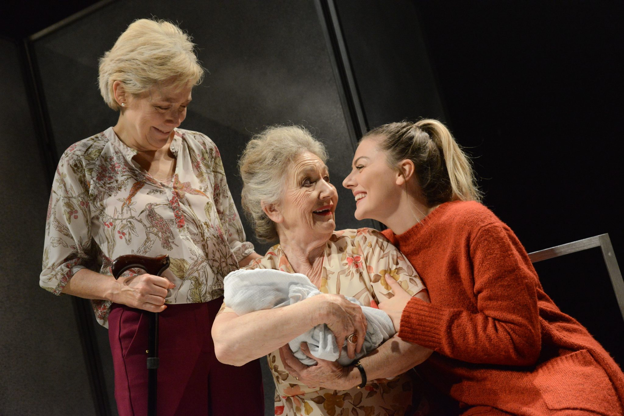 Photo shows all three characters, the grandmother is holding a new-born baby, looking at her granddaughter. Whilst the mother is looking over her shoulder all looking very happy.