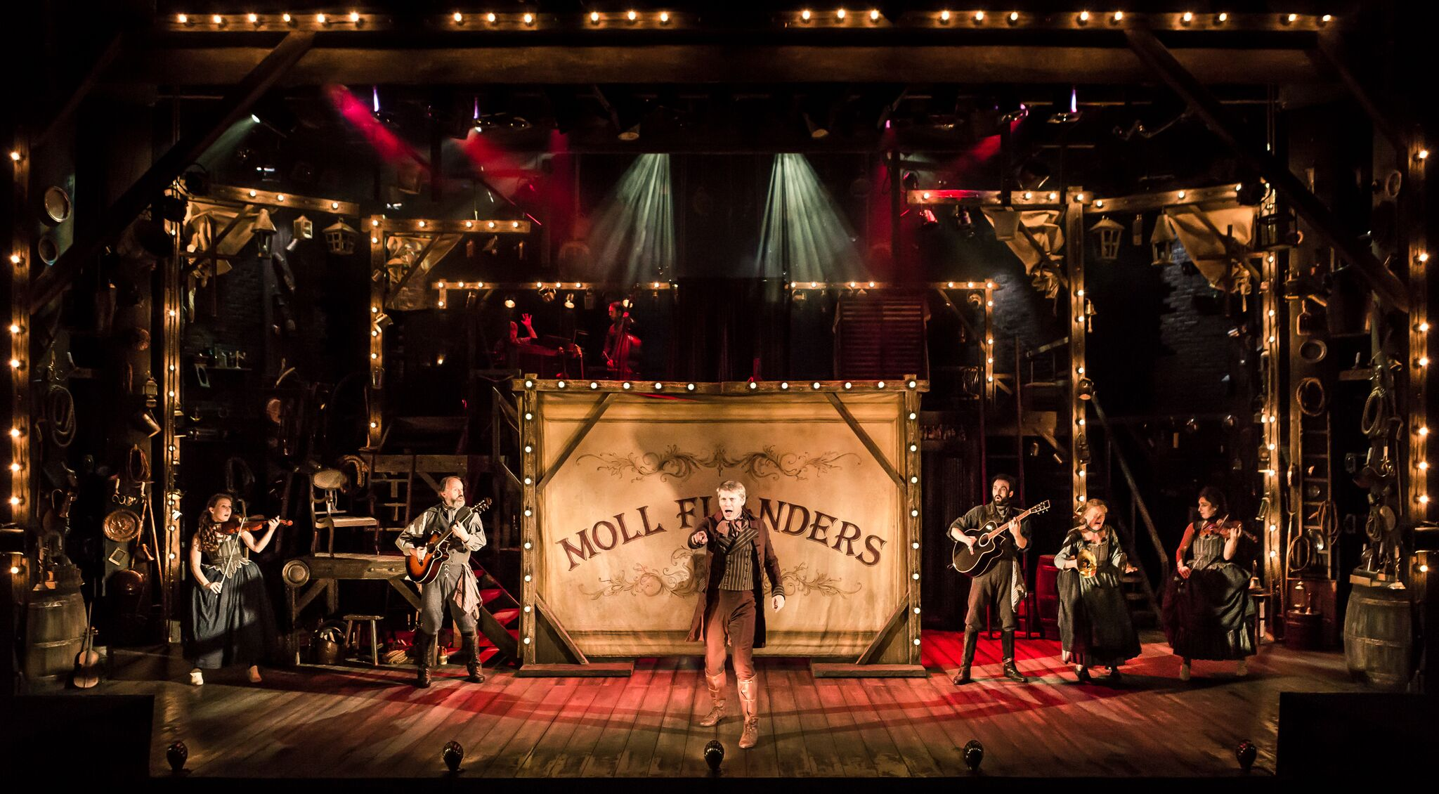 Photo shows full cast of stage, with the character 'Daniel DeFoe' setting the scene. The light is a mixture of reds and oranges. Daniel is standing centre stage with the title 'Moll Flanders' behind him on a canvas.