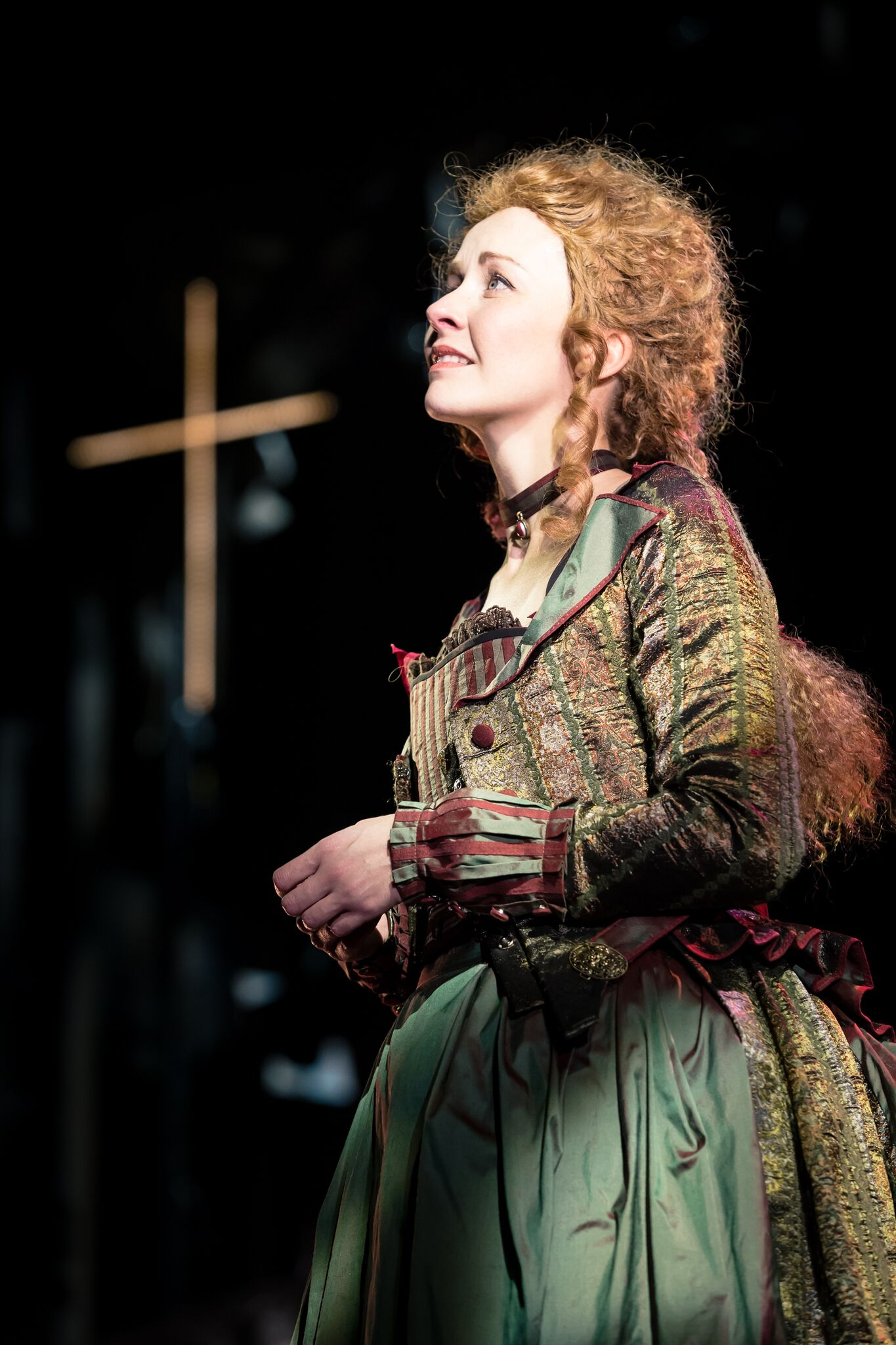Moll Flanders (Eva-Jane-Willis) is stnading in a church in a green and gold coat looking up into the distance, wondering what she should do with her life.