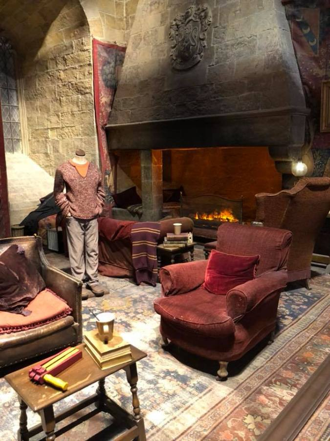 Photo shows the set of the Gryffindor common room with red arm chair and a roaring fire place in the background.