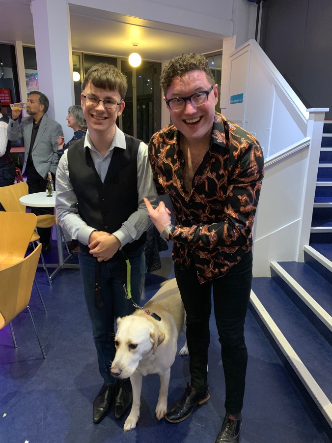 photo shows me and Antony-Stuart-Hicks after the show at the press party. Both me and antony are standing next to each other, with Guide Dog Blossom in the middle. Anthony is smiling very excitedly whilst pointing at me!
