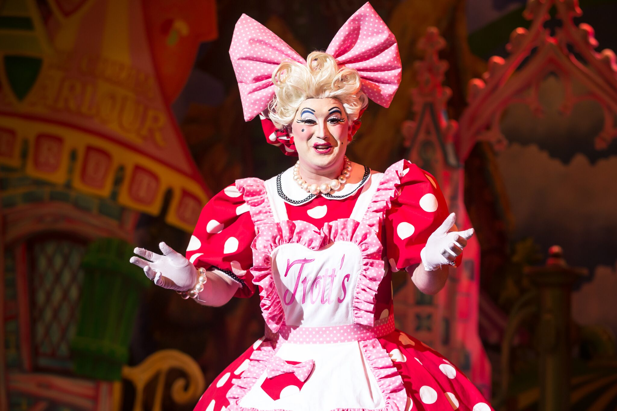 Photo shows Antony-Stuart-Hicks as 'Dolly Trott' she is a red polkadot dress with the base colour being bright red with white dots. She is also wearing a bright pink boe on her head.