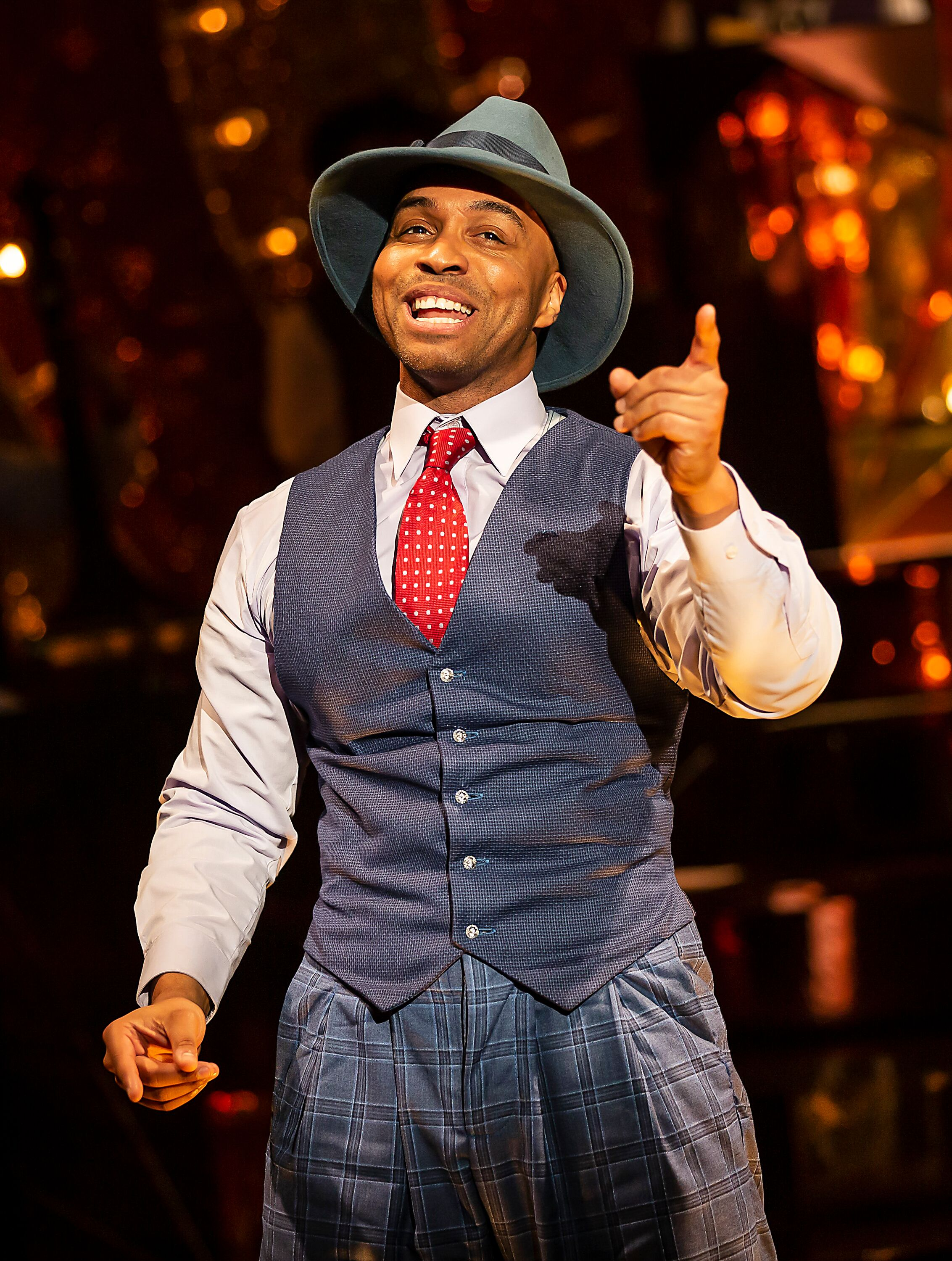 photo shows one of the male singers Wayne Robinson singing to the audience. He is wear a blue wastecoat with blue suit trousers, plain blue shirt, a red white dotted tie and a blue Fedora like hat.
