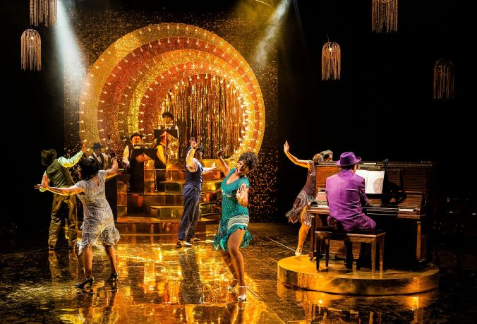 photo shows all the cast dancing and singing with a full band and piano playing the background