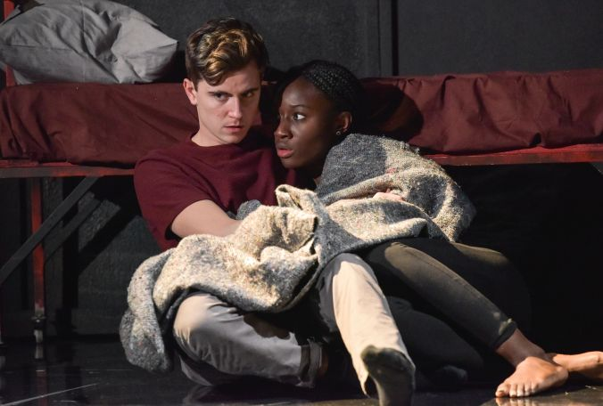 Photo shows Sephy' (Heather Agyepong) and Callum (Billy Harris) cuddling together, wrapped up in grey blanket. Sitting up against a red mental bed