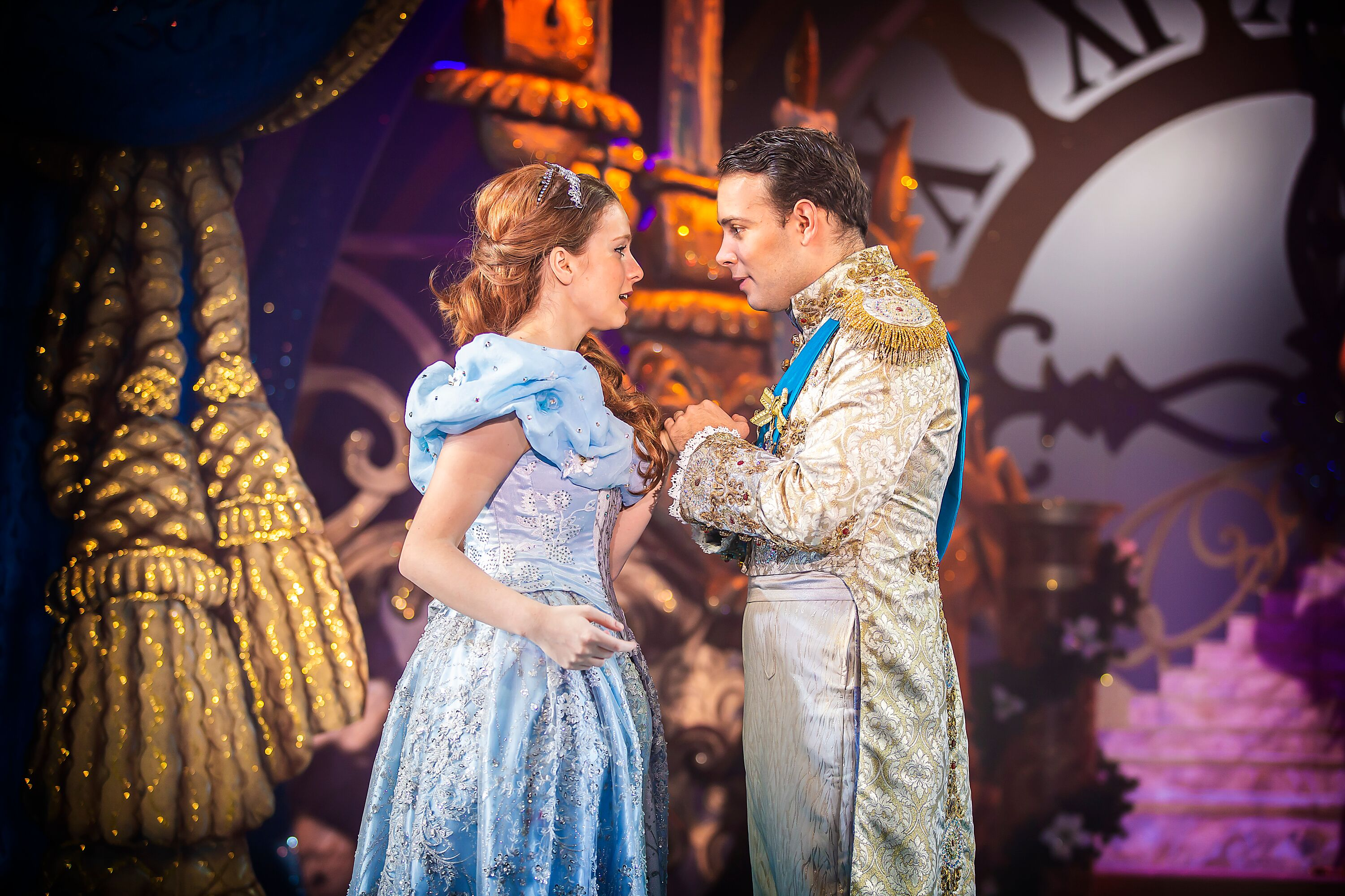Image shows Cinderella in her sky blue glittery ball gown, and the prince in his ball golden suit gazing into eachothers eyes! Photography By Pamela Raith