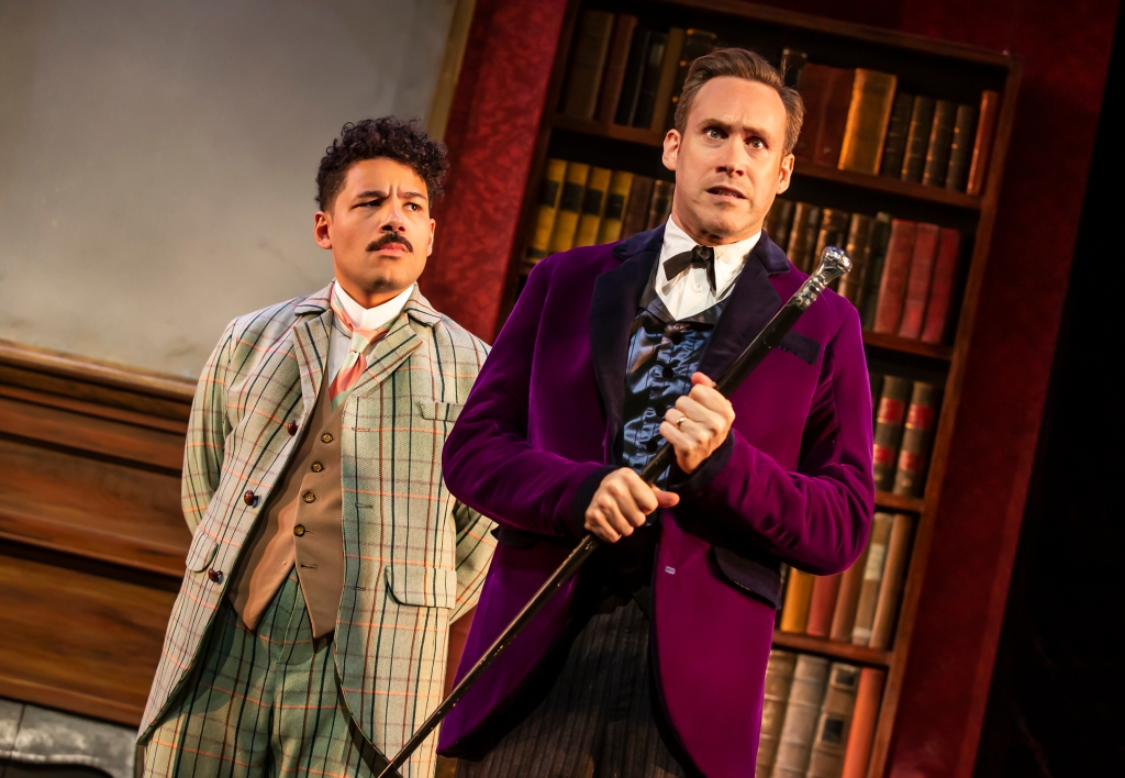 Imagine of Holmes in a purple blazer holding a black and silver cane, looking concerned, with Waston just behind him looking at Holmes expectantly.